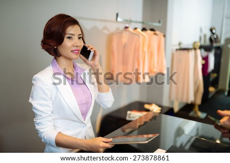 Pretty clothing shop manager calling on the phone - stock photo