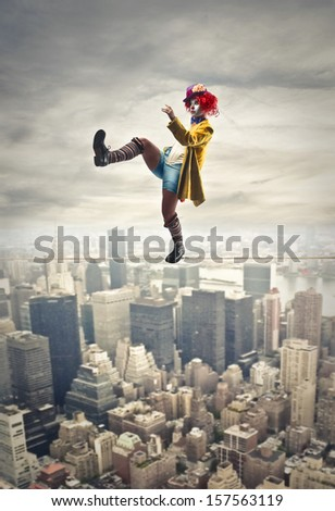 pretty clown walking on a tightrope above the city - stock photo