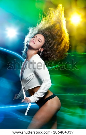 Pretty clubber dancing in a nightclub on colorful lighting background - stock photo