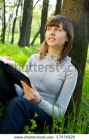 Pretty college girl studying a book on green meadow
