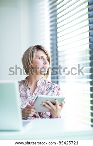 Pretty college student/businesswoman working on her tablet computer (shallow DOF; color toned image) - stock photo