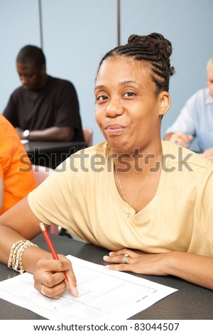 Pretty college student with Cerebral Palsy, taking a test in her adult education class. - stock photo
