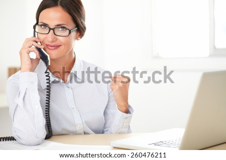 Pretty company secretary with glasses cheerfully conversing on the phone while using the computer in the office - stock photo