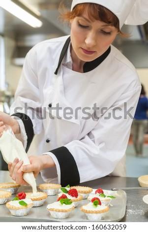 Pretty concentrated head chef preparing dessert in professional kitchen - stock photo