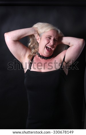 Pretty, confident, middle aged woman in her fifties having fun on a dark background - stock photo