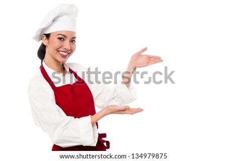 Pretty cook greeting the customers and directing them the way. - stock photo