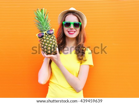 Pretty cool girl in sunglasses with pineapple having fun over colorful orange background - stock photo