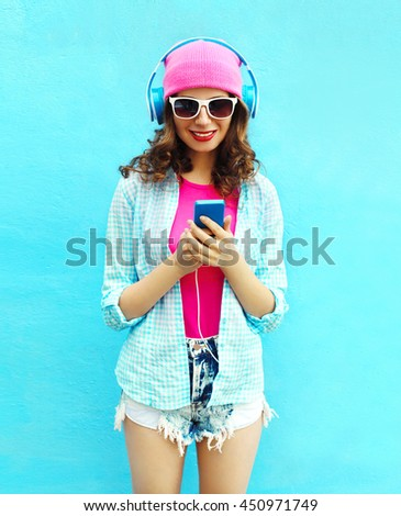 Pretty cool woman listens to music in headphones using smartphone over blue background - stock photo