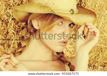 Pretty country girl wearing cowboy hat - stock photo