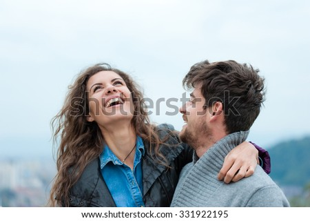 Pretty couple hugging and flirting, having a happy time. - stock photo