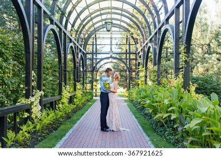 Pretty couple hugging and flirting in an urban park looking at each other a wreath on his head, holding flowers in their hands  summer - stock photo