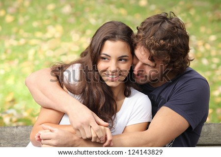 Pretty couple hugging and flirting in an urban park sitting in a bench and looking away - stock photo