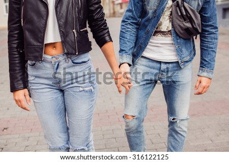 Pretty Couple in love ,lovely young blond woman having fun with her handsome hipster style boyfriend walking on the street,holding hands,traveling together,couple in jeans suit - stock photo
