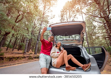 Pretty couple in sweaters and hats making selfie photo, sitting in the car trunk on the forest roadside. Young family traveling by car in the pine forest - stock photo