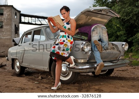 Pretty couple is trying to repair their old car using manual. Rural background.