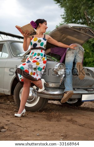 Pretty couple is trying to repair their old car using manual. Rural background. - stock photo