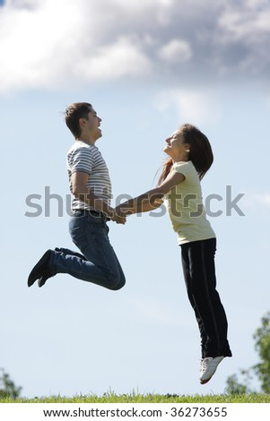 Pretty couple jumping up to clouds outdoor photo in sunlight