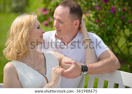Pretty couple sits and embrace on a bench in park outdoors