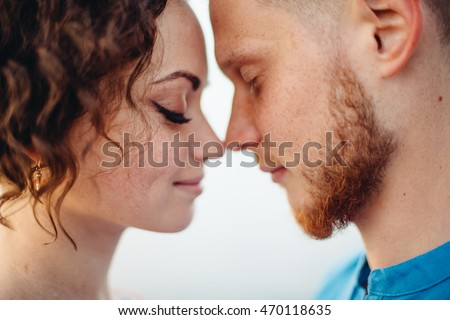 Pretty couple stands nose to nose with closed eyes