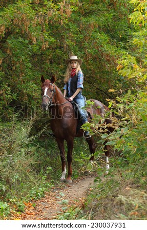 Pretty cowgirl on brown horse in autumn woods