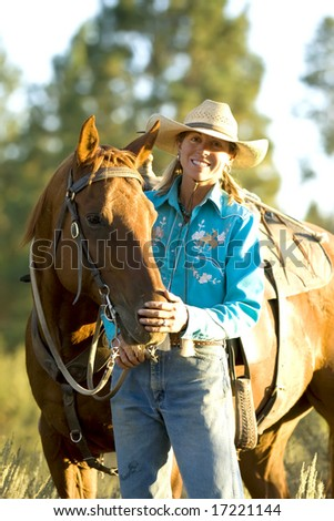 Pretty Cowgirl standing with her horse in the evening light - stock photo