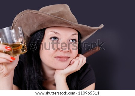 pretty cowgirl with a cigar and whiskey in his hand relax - stock photo