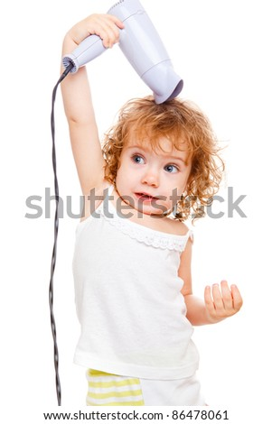Pretty curly toddler drying her hair - stock photo