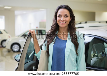 Pretty customer standing next to her car at new car showroom - stock photo