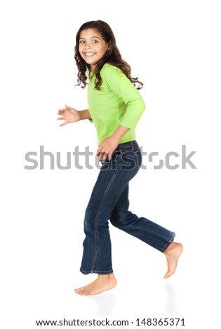 Pretty cute caucasian girl wearing a green long sleeve top and blue jeans is running and smiling at the camera. - stock photo