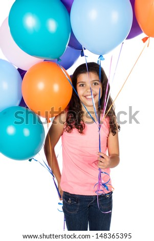 Pretty cute caucasian girl wearing a pink top and blue jeans. The girl is holding a bunch of bright coloured helium balloons. - stock photo