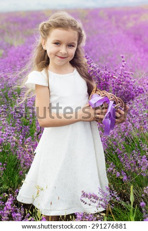 Pretty cute child girl is wearing white dress in a lavender field holding a basket full of purple flowers - stock photo