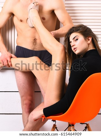 pretty cute sexy brunette girl in black bodysuit sitting on orange chair and put legs in beige shoes on muscle torso of athletic man in boxer brief on white studio background