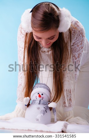 Pretty cute woman holding little snowman. Attractive girl in earmuffs and white sweater pullover in studio on blue. Winter fashion.