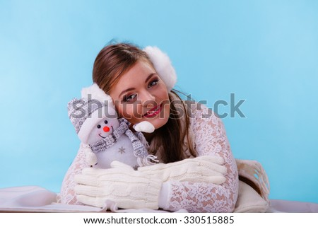 Pretty cute woman holding little snowman. Attractive girl in studio on blue. Winter.