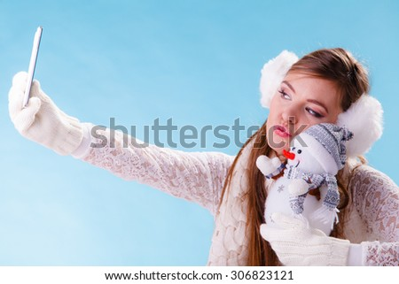 Pretty cute woman holding little snowman taking selfie self photo picture with camera. Attractive girl in earmuffs and white sweater pullover in studio on blue. Winter fashion.