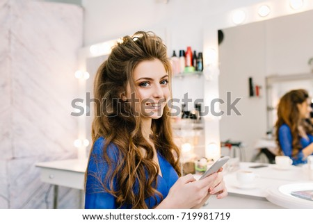Pretty cute young woman with long brunette hair smiling to camera in beauty salon. Beauty, preparing to party, celebration, luxury lifestyle, happiness, true positive emotions, coiffure