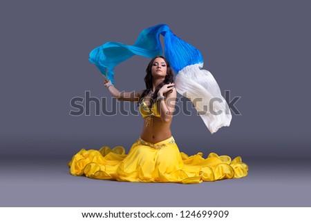 Pretty dancer in yellow costume sitting on floor - stock photo