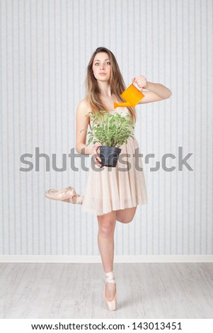 Pretty dancer with a watering can and a plant - stock photo