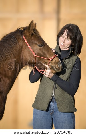 Pretty dark haired woman standing with her sorrel (chestnut) quarter horse foal against an out of focus barn. - stock photo
