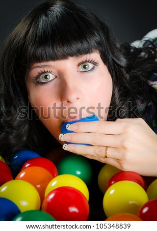 Pretty darkhaired girl surrounded by multicolored plasitc balls. She likes the taste of a blue one - stock photo