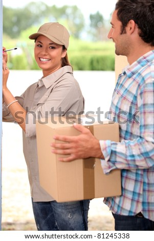 pretty delivery girl doing her job - stock photo