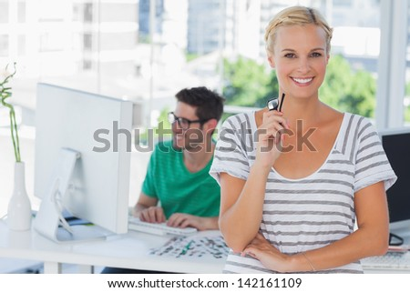 Pretty designer posing in his office with her colleague working behind - stock photo