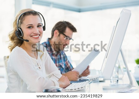 Pretty designer with headphone working on computer in office