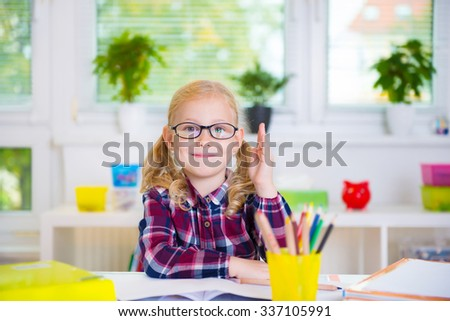 Pretty diligent girl in glasses learns at school - stock photo
