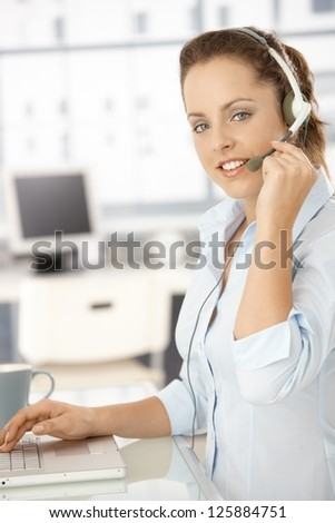 Pretty dispatcher working in office, using headset and laptop, smiling. - stock photo