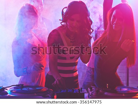 Pretty Dj girl playing songs in a disco - stock photo