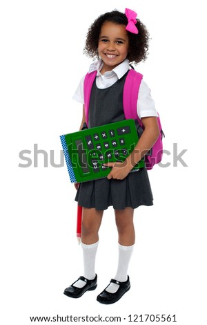 Pretty doll is ready for school. Smilingly facing camera. - stock photo