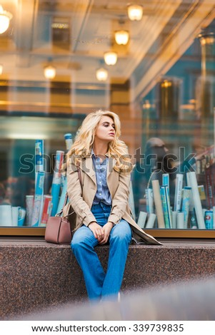 Pretty dreamy woman waiting for someone while sitting on shop sill in warm autumn day, charming blonde female posing against big shop window, young student girl relaxing after lectures in University  - stock photo