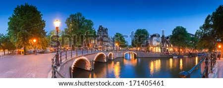 Pretty dutch doll houses illuminated at night and reflected in the tranquil canals of Amsterdam. - stock photo