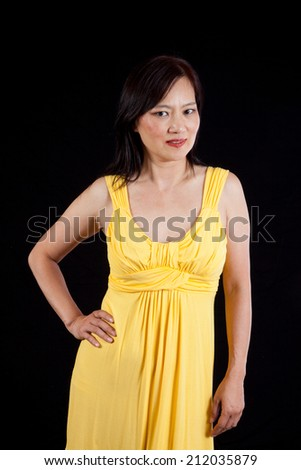 Pretty East Asian woman with long dark hair and a yellow dress, with her hand on her hip